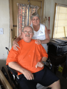 Man in orange shirt sitting in a wheelchair with a woman in a white blouse standing behind him with her hands on his shoulders.