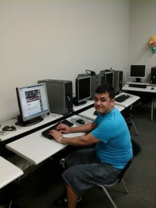 Young man with a bright blue shirt sitting at a computer in the computer classroom.